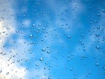 Regentropfen auf dem Glas mit undeutlichem blauem Himmel und weißer Wolke Lizenzfreie Stockfotos