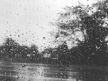 Regentropfen auf dem Glasfenster während des Regnens von Jahreszeitschwarzweiss-Farbe Lizenzfreie Stockfotografie