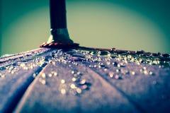 Regentropfen auf einem bunten Regenschirm mit allen Farben des Regenbogennahaufnahme Makro-waterdrops Hintergrundes lizenzfreies stockbild