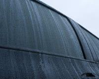 Regentropfen auf einem schwarzen Auto Stockbilder