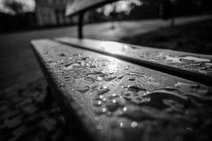 Regentropfen auf einer Bank Stockfotografie