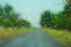 Regentropfen auf einer nassen Autowindschutzscheibe Stockbild