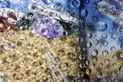 Regentropfen auf Farbhintergrund Stockfotos