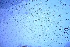 Regentropfen auf Fenster mit blauem Himmel Stockfotografie