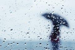 Regentropfen auf Fenster mit Person mit Regenschirm Stockfotografie