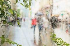 Regentropfen auf Fensterglas, wenige unerkennbare Leute hetzen nach Hause unter Regenschirmen, abstrakter unscharfer Hintergrund  Stockfoto