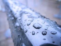 Regentropfen auf Geländer Stockfoto