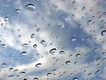 Regentropfen auf Glas und Himmel Stockfotos