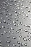 Regentropfen auf silberner Oberfläche Stockbilder