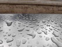 Regentropfen bilden Formen auf Metall stockfoto
