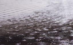 Regentropfen in den Regentropfen einer Pfütze in einer Pfütze lizenzfreies stockbild