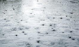 Regentropfen, die einer Pfütze plätschern. Stockfoto