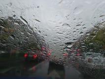 Regentropfen, die Streifen auf einer Windschutzscheibe bilden Stockbild