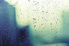 Regentropfen gegen ein Fenster Stockbilder