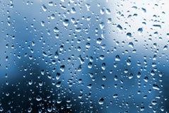 Regentropfen mit blauer Leuchte stockbild