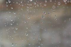 Regentropfen sind auf der anderen Seite des Glases Stockfoto