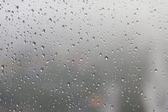 Regentropfen, Wasser fällt auf eine Glasoberfläche des Fensters Lizenzfreie Stockfotografie