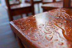 Regentropfentropfen über einem Holzstuhl stockfotos