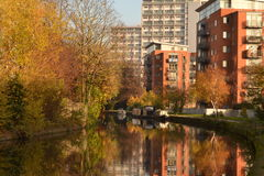Grand Union Canal London. Sunny winter day on Grand Union canal in London with trees on one side and blocks of flats on other Stock Photo