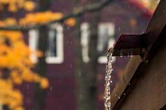 Regenwasser, das aus Dachspitze ausläuft lizenzfreies stockfoto