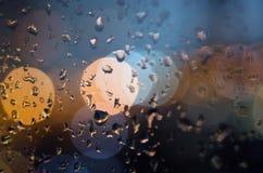 Regenwassertröpfchen auf dem Fenster mit unscharfem bokeh Hintergrund Lizenzfreie Stockfotografie