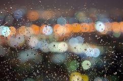 Regenwassertröpfchen auf dem Fenster mit unscharfem bokeh Hintergrund Lizenzfreie Stockfotos