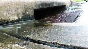 Regenwater die een onweersafvoerkanaal tegenkomen stock footage
