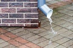 Regenwater die van downspout stromen stock afbeeldingen