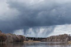 Regenwolken über dem Wald und dem Fluss Lizenzfreies Stockfoto