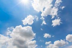 Regenwolken kommen auf den bunten blauen Himmel mit wirklichem Strahl der Sonne stockfotografie