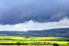 Regenwolken ziehen über Rapssamenfelder und -berge Stockbild