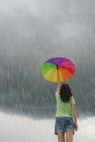 Regenzeit und Mehrfarbenregenschirmfrau Stockfoto