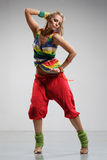 Reggae dancer. Rastafarian style dancer posing on a grey background Royalty Free Stock Images