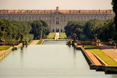 Water basins lead to the huge Royal Palace of Caserta in Campania royalty free stock image