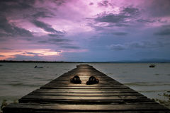 Reggie Perrin. Wooden Jetty floating out onto a lake with shoes on the jetty and a colourful sunset in the background stock photos
