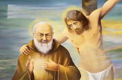 Reggio Emilia - het moderne schilderen van Pater Pio met de Jesus op corss in dei Cappuchini van kerkchiesa Stock Afbeelding