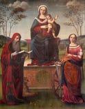 REGGIO EMILIA, ITALIA - 12 DE ABRIL DE 2018: La pintura de Madonna en el trone con el niño y el St Jerome y st Catherine en los D imagen de archivo