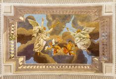 REGGIO EMILIA, ITALY - APRIL 13, 2018: The ceiling fresco of angels with the trumphs in church Chiesa di San Pietro. By Anselmo Govi stock photos
