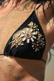 Reggiseno e pelle del costume da bagno con il primo piano della sabbia Fotografie Stock