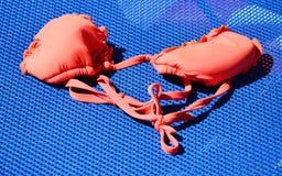 Reggiseno rosso su un sedile della spiaggia Immagine Stock