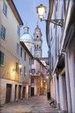 Reggo Emilia - a rua da cidade velha no crepúsculo com a igreja de San Giorgio imagem de stock