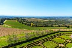 Região do Chianti, Itália - 21 de abril de 2018: Paisagem rural da terra, árvores de cipreste, vinhedos e oliveiras de Castello d imagem de stock royalty free