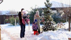 REGIÓN DE CHERKASY, UCRANIA, EL 25 DE DICIEMBRE DE 2018: invierno, escarchado, nevoso, día soleado Familia feliz con los pequeños metrajes