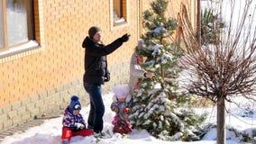 REGIÓN DE CHERKASY, UCRANIA, EL 25 DE DICIEMBRE DE 2018: invierno, escarchado, nevoso, día soleado Familia feliz con los pequeños almacen de video