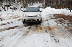 Región de Irkutsk, Rusia - marzo, 21 2016: Coche blanco en el camino nevoso de la primavera Fotos de archivo libres de regalías