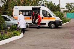 REGIÓN de KIEV, UCRANIA - 12 de mayo de 2016: ambulancia y una enfermera en la calle La ambulancia está cerca del hospital Fotografía de archivo