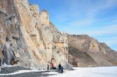 Región de Siberia, Irkutsk, cabo Sagan-Zaba, Rusia, marzo, 10, 2017 Turistas que caminan en la costa del lago Baikal Paisaje de l Imagen de archivo libre de regalías