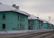 Región urbana de las pequeñas casas idénticas viejas la ciudad de Ob a lo largo de la calle un día de invierno gris, cubierto foto de archivo