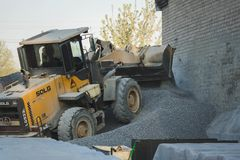 Regi?o de Voronezh, R?ssia, abril, 25 2019 As cargas do trator esmagaram de pedra na produ??o de concreto Corredor amarelo do car fotografia de stock