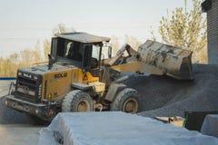 Regi?o de Voronezh, R?ssia, abril, 25 2019 As cargas do trator esmagaram de pedra na produ??o de concreto Corredor amarelo do car fotos de stock